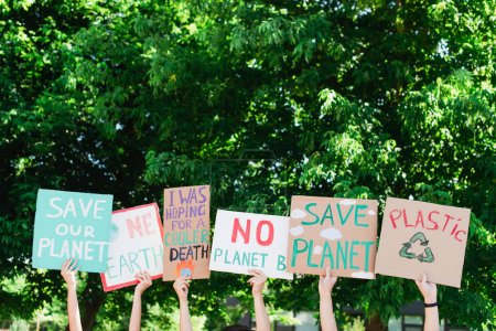 People holding placards with save planet and plastic recycle lettering with trees at background, ecology concept