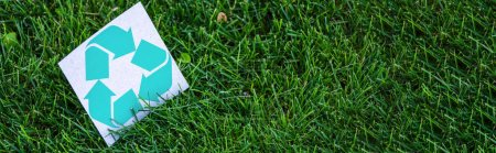 Panoramic shot of card with recycle symbol on grass outdoors, ecology concept