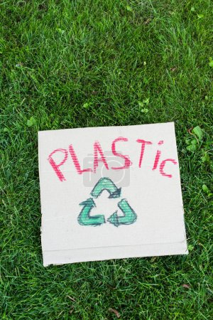Photo for Top view of placard with plastic lettering and recycle sign on grass, ecology concept - Royalty Free Image