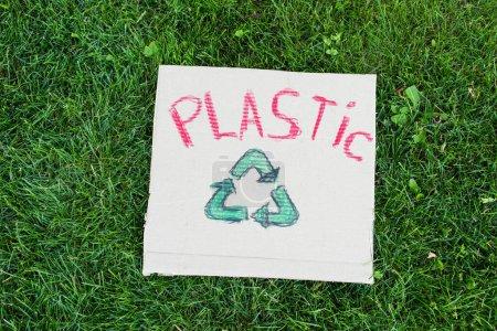 Górny widok znaku recyklingu i plastikowe napisy na tabliczce na zielonej trawie, koncepcja ekologii