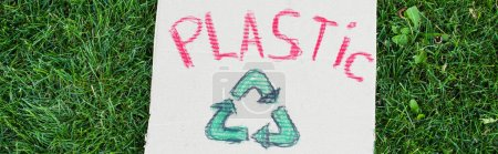 Horizontal crop of plastic lettering and recycle sign on placard on green grass outdoors, ecology concept