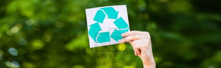 Panoramic crop of man holding card with recycle symbol outdoors, ecology concept