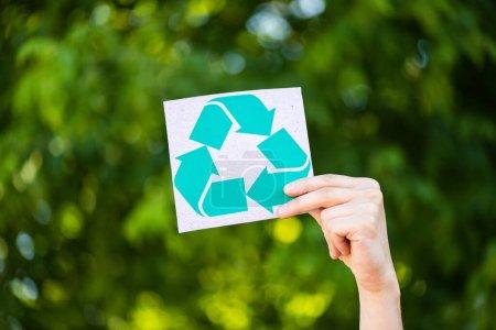 Photo pour Vue recadrée de l'homme tenant la carte avec signe de recyclage à la main à l'extérieur, concept d'écologie - image libre de droit