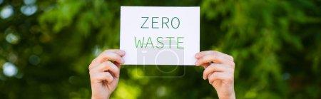 Photo pour Culture horizontale de l'homme tenant la carte avec zéro déchet lettrage à l'extérieur, concept d'écologie - image libre de droit