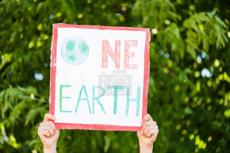 Cropped view of man holding placard with one earth lettering with trees at background, ecology concept