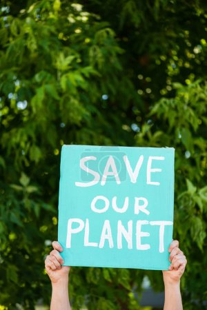 Cropped view of man holding placard with save our planet lettering with trees at background, ecology concept
