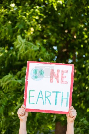 Cropped view of man holding placard with one earth lettering in hands with trees at background, ecology concept