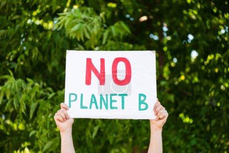 Ausgeschnittene Ansicht des Menschen mit Plakat ohne Planet-B-Schriftzug mit Bäumen im Hintergrund, Ökologiekonzept