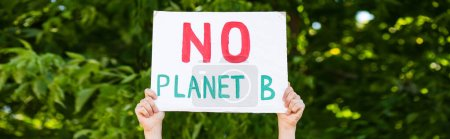 Photo for Horizontal crop of man holding placard with no planet b words with trees at background, ecology concept - Royalty Free Image