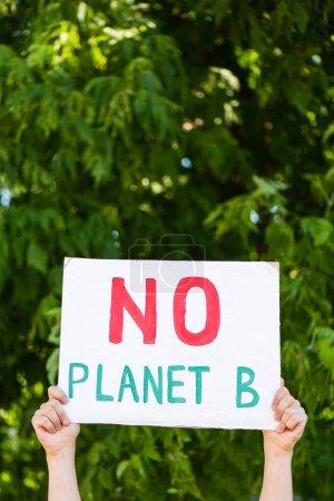 Vue recadrée de l'homme tenant une pancarte sans planète b lettrage dans les mains avec des arbres en arrière-plan, concept d'écologie