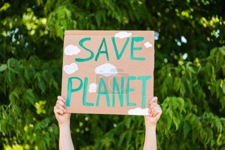 Widok człowieka trzymającego tabliczkę z ocalałą planetą z drzewami w tle, koncepcja ekologii