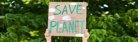 Panoramiczne ujęcie człowieka trzymającego tabliczkę z zapisaną planetą z drzewami w tle, koncepcja ekologii