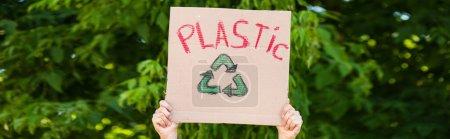 Photo pour Culture panoramique de l'homme tenant la plaque avec panneau de recyclage et lettrage en plastique avec des arbres à l'arrière-plan, concept écologique - image libre de droit