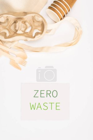 Photo for Top view of bag, paper cups and wooden cutlery near card with zero waste lettering on white background, ecology concept - Royalty Free Image