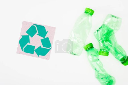 Photo for Top view of card with recycle sign near crumpled plastic bottles on white background, ecology concept - Royalty Free Image