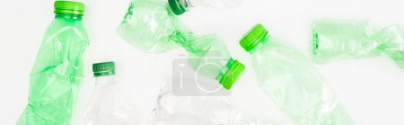 Panoramic orientation of crumpled plastic bottles on white surface, ecology concept