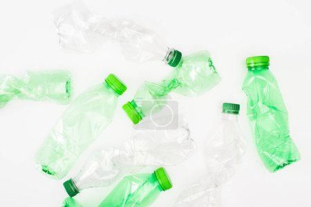 Top view of crumpled plastic bottles on white surface, ecology concept