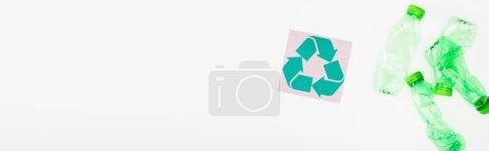 Foto de Cultivo horizontal de botellas de plástico arrugadas cerca de la tarjeta con símbolo de reciclaje sobre fondo blanco, concepto de ecología - Imagen libre de derechos