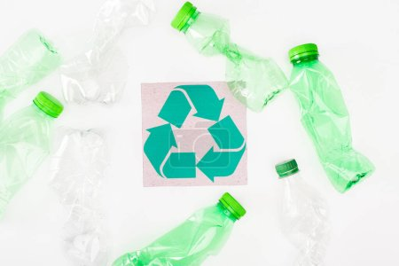 Top view of crumpled plastic bottles near card with recycle sign on white background, ecology concept