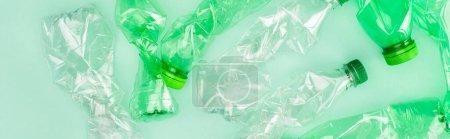 Photo pour Culture horizontale de bouteilles en plastique froissées sur surface verte, concept écologique - image libre de droit