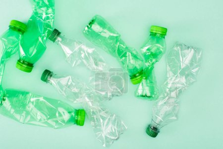Top view of crumpled plastic bottles on green background, ecology concept