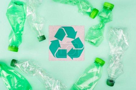 Photo pour Vue du dessus de la carte avec panneau de recyclage près des bouteilles froissées sur fond vert, concept d'écologie - image libre de droit
