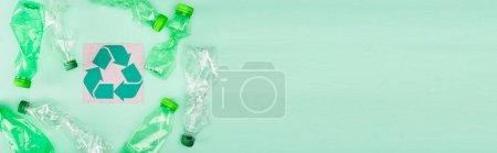 Foto de Concepto panorámico de botellas plásticas arrugadas cerca de la tarjeta con símbolo de reciclaje sobre fondo verde, concepto de ecología - Imagen libre de derechos