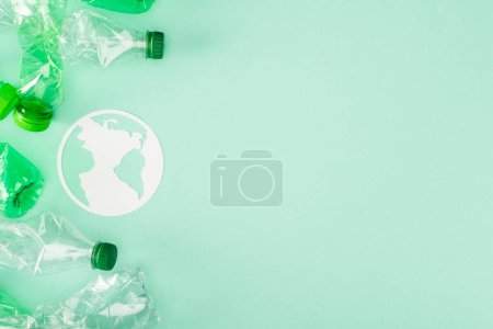 Photo for Top view of paper earth sign near crumpled plastic bottles on green background, ecology concept - Royalty Free Image
