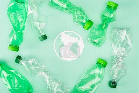 Photo pour Vue du dessus du panneau planète papier près des bouteilles en plastique froissées sur la surface verte, concept d'écologie - image libre de droit