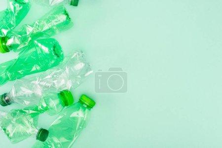 Photo pour Vue du dessus des bouteilles en plastique froissées sur fond vert avec espace de copie, concept écologique - image libre de droit