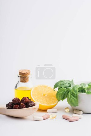 Photo pour Feuilles vertes au mortier, baies et citron près des pilules sur fond blanc, concept de naturopathie - image libre de droit