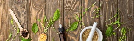 Photo pour Vue du dessus des pilules dans les cuillères, mortier, herbes vertes et bouteille sur la surface en bois, concept de naturopathie - image libre de droit