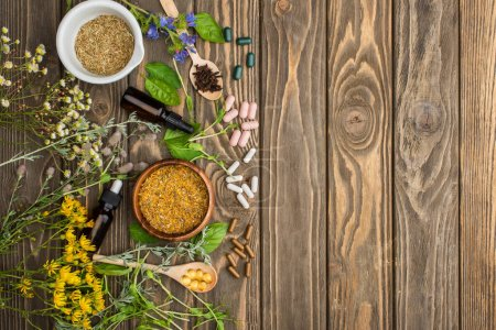 Photo for Top view of pills in spoons, green herbs and wildflowers on wooden surface, naturopathy concept - Royalty Free Image