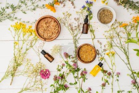 Photo pour Vue de dessus des herbes dans des bols près des fleurs et des bouteilles sur fond blanc en bois, concept de naturopathie - image libre de droit