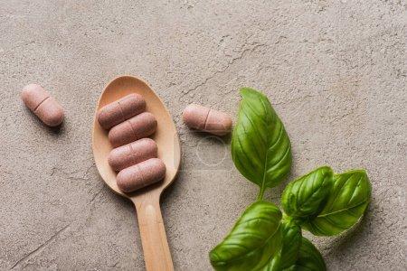 Photo pour Vue du dessus des feuilles vertes et des pilules dans une cuillère en bois sur fond de béton, concept de naturopathie - image libre de droit