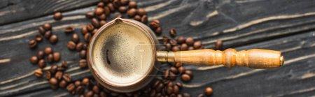 Photo pour Vue de dessus de cezve avec café sur grains de café sur la surface en bois, vue panoramique - image libre de droit