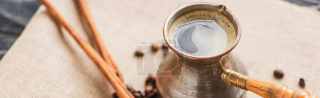selective focus of cezve with coffee near cinnamon sticks and coffee beans on sackcloth, panoramic shot