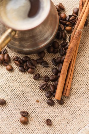 close up view of cezve with coffee near cinnamon sticks and coffee beans on sackcloth
