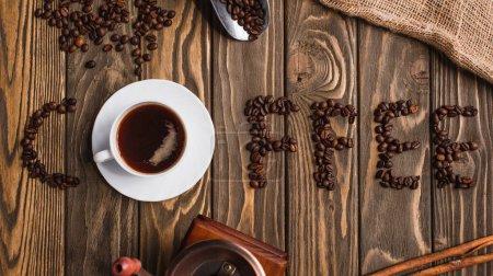 Photo pour Vue du dessus de tasse de café sur la soucoupe et lettrage de café en grains sur la surface en bois - image libre de droit
