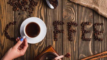 Photo pour Vue recadrée d'une femme tenant une tasse de café sur une soucoupe près d'un lettrage de café fait de grains sur une surface en bois - image libre de droit