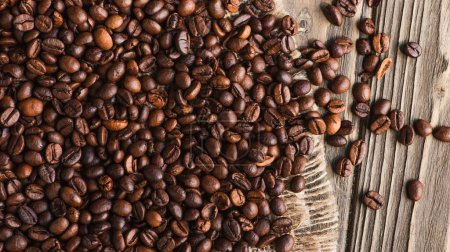 Photo pour Vue de dessus des grains de café éparpillés sur la toile de jute sur la surface en bois - image libre de droit