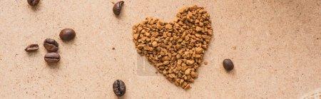 Photo pour Vue de dessus du coeur faite de café instantané près des grains de café sur la surface beige, vue panoramique - image libre de droit