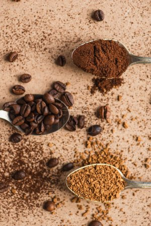 top view of ground, instant coffee and beans in spoons on beige surface