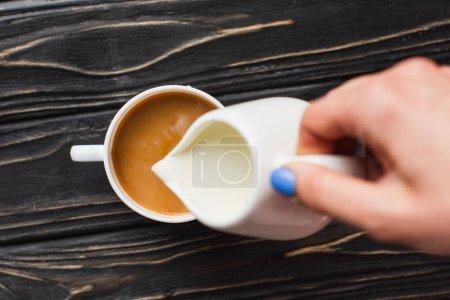 Photo pour Vue recadrée du barista ajoutant du lait au café dans une tasse sur une surface en bois - image libre de droit