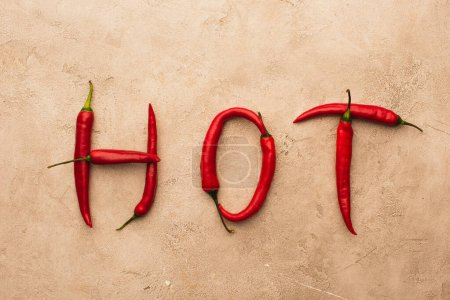 top view of word hot made of chili peppers on beige concrete surface