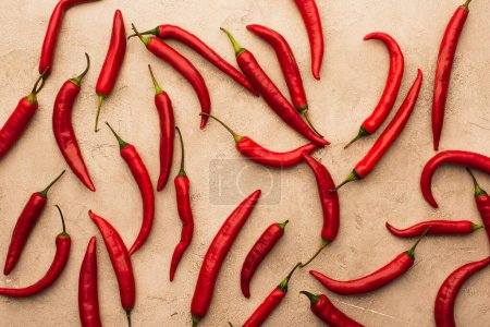 Photo for Top view of scattered chili peppers on beige concrete surface - Royalty Free Image