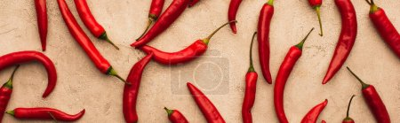 top view of scattered chili peppers on beige concrete surface, panoramic shot