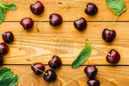Photo for Top view of wet ripe sweet cherries with green leaves on wooden surface - Royalty Free Image