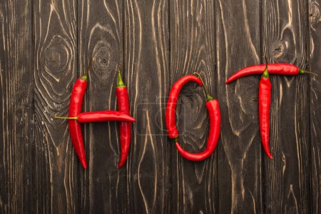 top view of word hot made of chili peppers on wooden surface