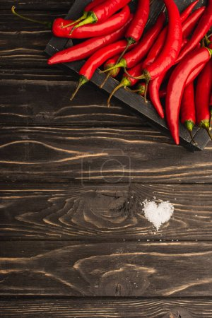 top view of chili peppers in box near salt heart on wooden surface